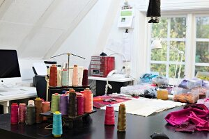 Various reels of thread and fabric remnants on sewing table in office