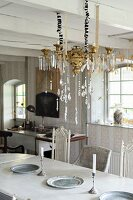 Brass chandelier with glass pendants suspended above dining table from white wooden ceiling