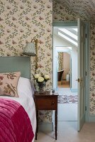 Romantic bedroom with floral wallpaper, antique bedside table and view through open door