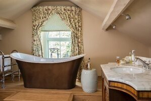 Attic bathroom with free-standing bathtub, porcelain stool and marble washstand