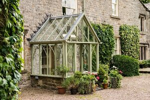 Glass porch in style of Victorian greenhouse over front door of stone house