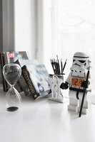 Glass hour glass and stormtrooper toy on desk