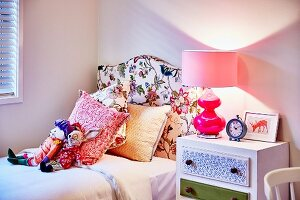 Soft toys and scatter cushions on bed with headboard upholstered in floral fabric and pink table lamp on bedside cabinet
