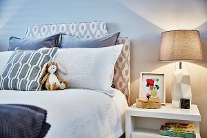 Scatter cushions and rabbit soft toy on double bed with upholstered headboard; table lamp on white bedside table