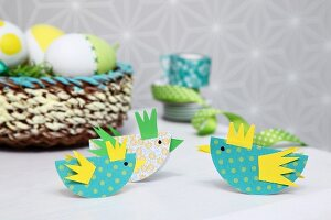 Easter arrangement in yellow and green; colourful, paper chicks as place cards