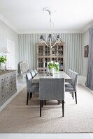 Elegant dining room with glass-fronted cabinet, wood-clad walls and subtle shades of grey
