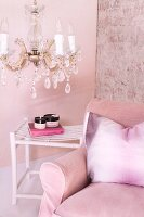 Pink armchair with scatter cushion and side table below crystal chandelier against pink-painted wall