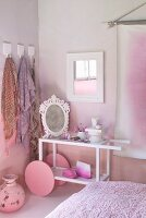 Modern serving trolley with large wheels used as dressing table and painted pink against pink wall