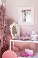 Mirror and cosmetics on serving trolley used as dressing table against pink-painted wall