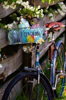 Old bicycle with picnic basket leaning against wooden fence