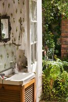 Washstand against floral wallpaper and next to open door leading into garden