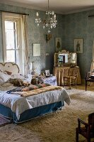 Dressing table, chandelier and bed in vintage-style blue bedroom