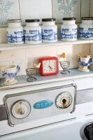 Vintage spice jars, egg cups and clock above cooker in kitchen