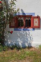 Fassadenausschnitt mit blauer Fasche um Fenster eines restaurierten Bauernhauses