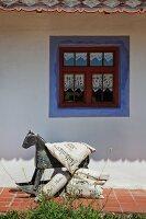 Vintage Schaukelpferd und Kissen mit nostalgischen Schriftzügen vor Bauernhaus mit blauer Fenster-Fasche