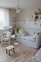 Rocking chair and sofa with striped pastel cover in Scandinavian country-house style