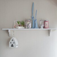 Romantic, country-house Easter arrangement of spring flowers and house-shaped lantern on small bracket shelf