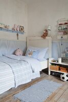 Pale blue walls and shabby-chic bed in boy's bedroom