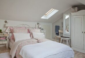 Romantic double bed with pink bed linen in shabby-chic attic room