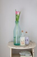 Tulips in old milk bottle and small bottles with vintage-style labels on small, vintage, wall-mounted shelf