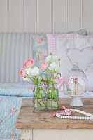 Ranunculus in glass bottles in wore frame, bead heart and glass cover on cake stand on old table in front of sofa