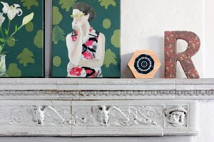 Vintage mantelpiece decorated with modern artworks and decorative letter