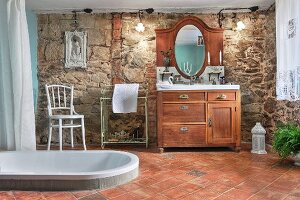 Spacious bathroom with sunken bathtub in terracotta floor, rustic washstand and stone wall