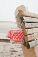 Candle lantern with coral-pink crocheted cover hung from backrest of wooden bench on beach