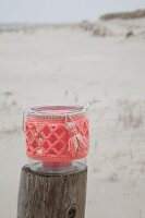 Candle lantern with coral-pink crocheted cover on wooden post on beach