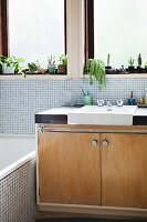 Pale wooden retro washstand with integrated sink below window; pale mosaic tiles on wall and bathtub cladding