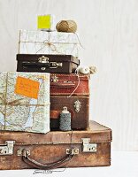 Vintage suitcases of various sizes and packages wrapped in wrapping paper made from old maps