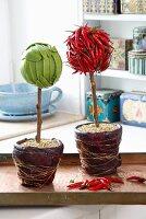 Aus Zuckerschoten und aus Chilischoten gebastelte Blumen, im Topf