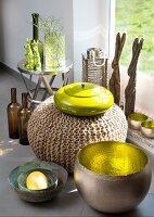 Verschiedene Behälter im Materialmix, Metallschale mit vergoldeter Innenseite vor Sitzpouf und gelbe Keramikdose mit Deckel