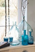 Various clear and blue glass bottles and twigs in front of window