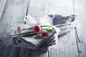Grey linen napkin and bellis daisies tied with white ribbon on wooden surface