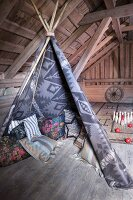 Floor cushions in teepee in rustic attic room with exposed wooden roof structure