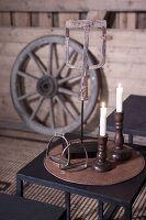 Lit white candles in wooden candlesticks and vintage stirrups on black side table