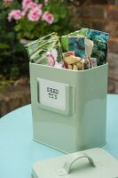 Vintage-style metal tin of seed packets on table in garden