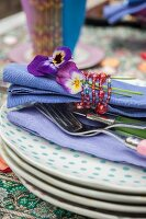 Violas and blue linen napkin tied with beaded napkin ring on stack of plates