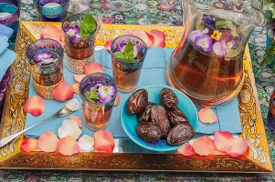 Tray of tea glasses, jug and dates scattered with petals