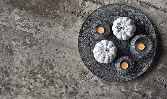 Ornamental squashes painted black and white and tealights in bowls