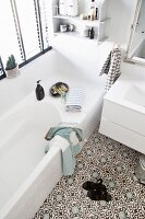 White bathroom with Moroccan-style ornamental floor tiles and wall-mounted shelves above bathtub