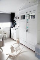 White-painted retro and vintage furniture, grey roller blind, black curtains and star-patterned wallpaper in nursery
