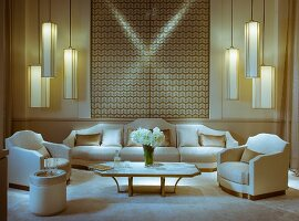 Formal arrangement of armchairs, sofa set, coffee table and groups of pendant lamps in front of geometric wall hanging in white and gold