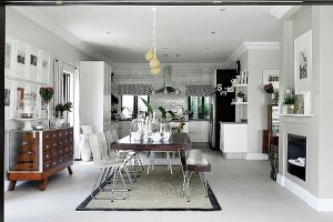 Dining table with matching bench and white chairs in open-plan interior with traditional ambiance; open-plan kitchen in background