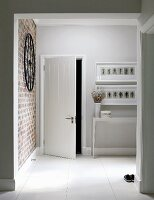 Foyer with open door and console table below drawings in white frames
