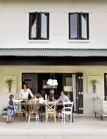 House with open, sliding, folding doors and roofed terrace; family sitting around table on various chairs