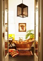 View through open double doors of free-standing copper bathtub, portrait of man and South-American-style accessories on floor