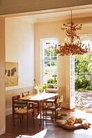 Dining table, various chairs and dog lying on floor in front of open terrace doors leading to sunny courtyard