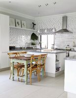 Vintage kitchen table and wooden chairs next to free-standing central island in modern, open-plan kitchen with white fronts
